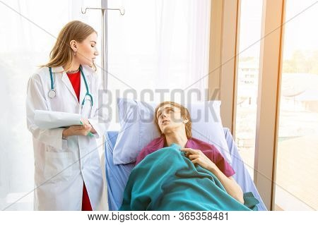 Doctor Examining The Symptoms Of A Patient Lying On A Patient Bed.
