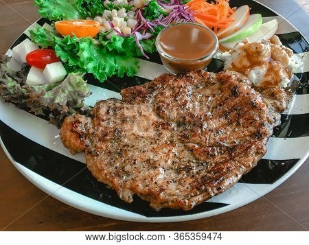 Pork Steak Topped With Pepper Served With Mashed Potato, Salad Vegetable And Gravy Sauce.