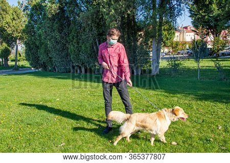 Boy Wearing Virus Mask   With His Dog Playing At Garden