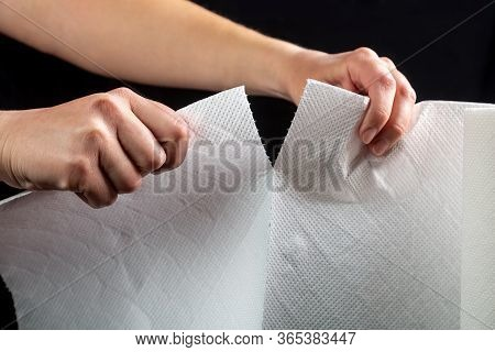 Hands Tear Off A Piece Of White Paper Towel From A Roll On A Black Background. Horizontal Orientatio