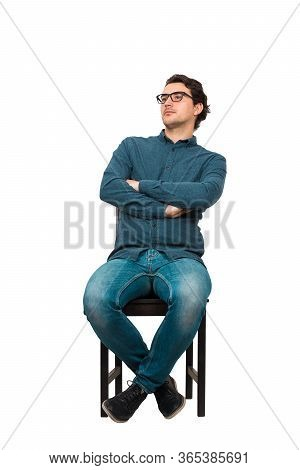 Full Length Portrait Of Confident Businessman Seated Relaxed On A Chair, Wearing Eyeglasses And Keep