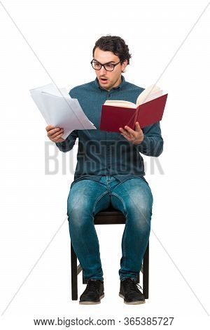 Full Length Of Perplexed Student Looking Stunned At Paper Projects And Book In His Hands, Seated On