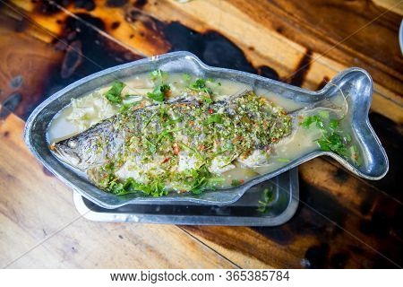 Steamed Sea Bass Fish With Lemon, Thai Famous Local Food Served On Fish Shape Plate. Thai Recommend