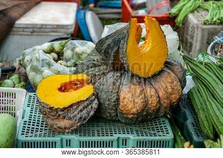 Selling On The Open Market In The Street A Green Ornamental Cut Pumpkin With Seeds Surrounded By Oth