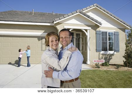 Portrait of happy middle aged couple with daughters in front of new house