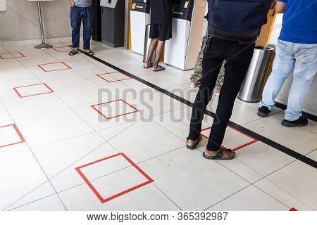 People Practicing Social Distancing In Queue Towards Auto Teller Machine In Bank