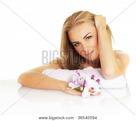 Portrait of attractive female in spa salon, photo of beautiful young lady with blond hair holding pink orchid flower, cute girl with natural makeup, day spa, health and beauty treatment, skincare