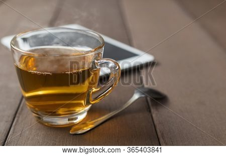Close Up Hot Tea Cup On Wood Table With Tea Spoon And Tablet Shot On Moning Time . Soft Focus And Se