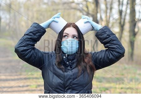 Covidiot Concept. Young Woman In Protective Mask Holds Many Rolls Of Toilet Paper Outdoors In Spring