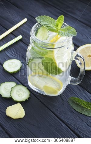 Sassy  Water  Slimming Or Infused Water With Lemon, Cucumber And Ginger In The Glass On The Black Wo