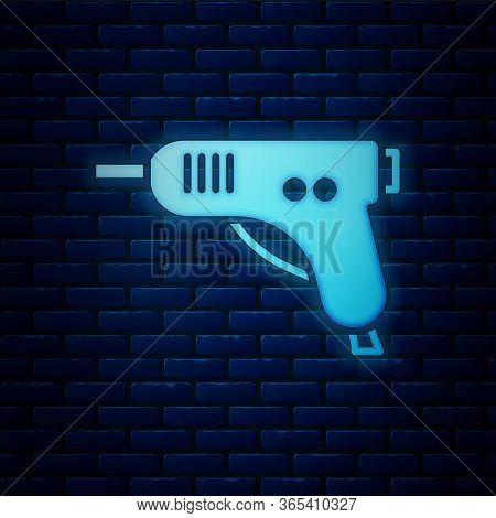 Glowing Neon Electric Hot Glue Gun Icon Isolated On Brick Wall Background. Hot Pistol Glue. Hot Repa