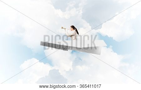 Elegant Woman Musician Playing Trumpet Brass. Young Businesslady In White Business Suit Flying In Pa