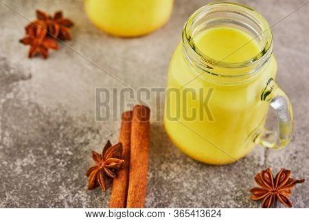 Golden Latte Turmeric Healthy Drink In A Glass Cup. Golden Milk With Turmeric, Cinnamon Sticks, Turm