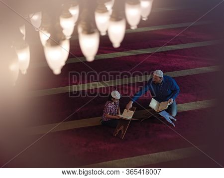 muslim prayer father and son in mosque praying and reading holly book quran together islamic education concept