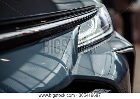 Closeup Of A Car Headlight. Headlight Of An Expensive New Car At A Car Dealership.