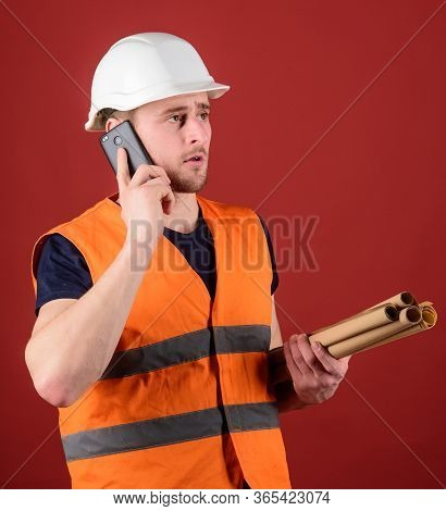 Architect Concept. Engineer, Architect, Builder On Busy Face Speaks On Smartphone While Holds Bluepr