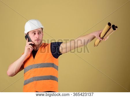 Man Supervises Construction On Phone, Ocher Background. Engineer, Architect On Busy Face Speaks On P