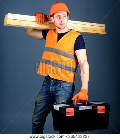 Woodworking Concept. Man In Helmet, Hard Hat Holds Toolbox And Wooden Beams, Grey Background. Carpen