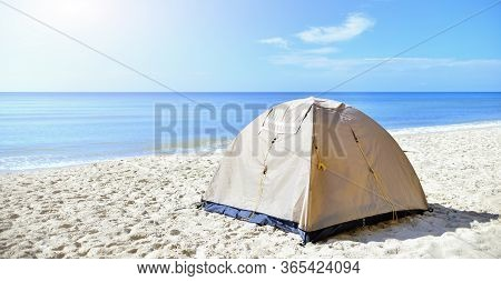 Sand-colored Tourist Tent On The Seashore In The Sand. Calm Morning Sea. Camping With A Tent At A Lo