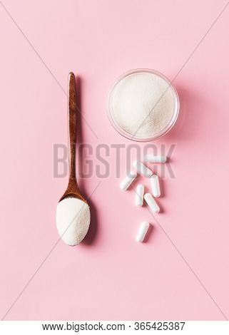 Collagen Powder In Wooden Spoon, Supplement With Capsule, Healthy And Anti Age Concept  On Pink Back