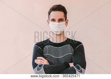 Portrait Confident Sports Man In Medical Face Mask Keeping Arms Crossed And Smiling Against Backgrou