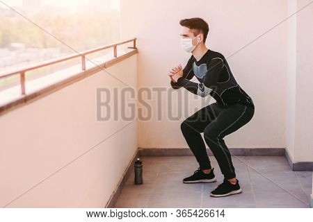 Young Athletic Man Fitness Instructor In Medical Face Mask Squatting At Balcony. Confident Sports Ma