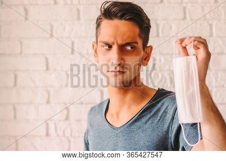 Portrait Angry Young Man With Funny Sun Tanned Lines On Face After Wearing Medical Face Mask. Confus