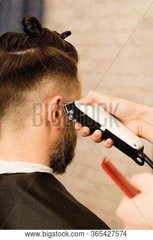 Male Haircut Electric Razor. Hand Of Hairdresser Shaves Hair With Electric Shaver. Hipster Man Getti