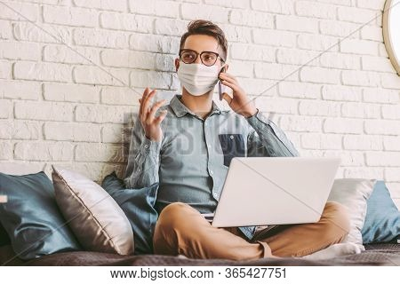 Happy Hipster Man Freelancer In Medical Face Mask Talking Mobile Phone, Sitting On Couch With Laptop
