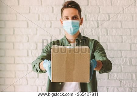 Happy Delivery Service Employee In Protective Mask, Rubber Gloves Giving Cardboard Box To Customer.
