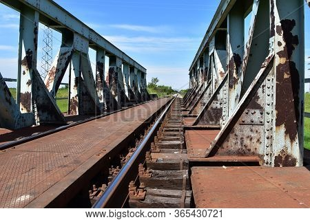 Old Abandoned Rusty Metal Rail Bridge With Wooden Planks