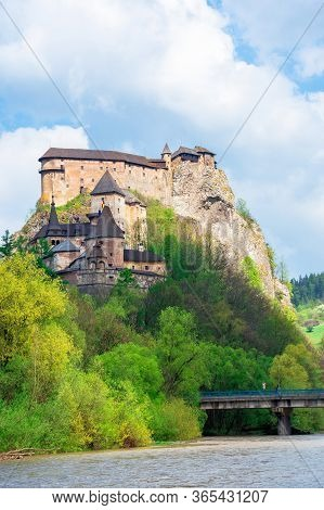 Medieval Orava Castle On The Hill. Beautiful Springtime Scenery In Dappled Light Above The River. Po