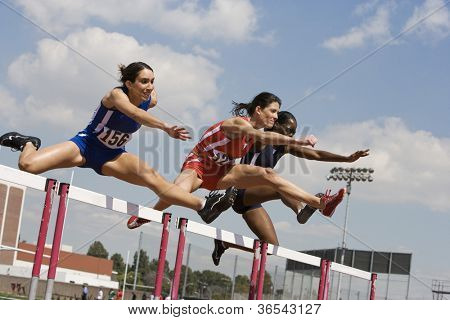 Three female athletes clearing hurdles in race