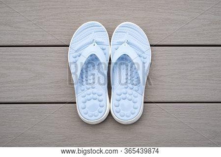 Light Blue Flip Flops On Gray Deck Background