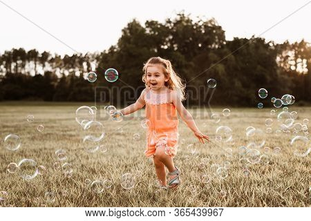 Little Girl In Orange Romper Catching Soap Bubbles On Grass In A Field At Sunset.