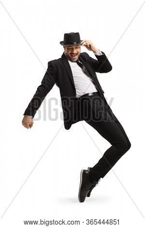 Man in a suit and hat dancing and standing on tiptoes isolated on white background