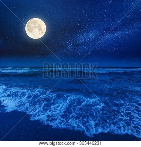 Beach And Sea On A Cloudy Night. Beautiful View Of Waves Rolling The Coast Beneath A Glowing Sky In