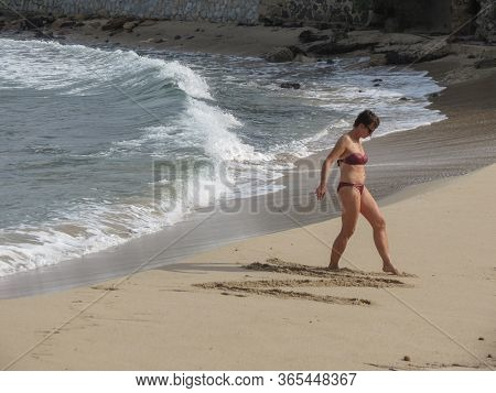 Cagliari, Italy - Circa October 2019: Unidentified Woman Writing On The Sand