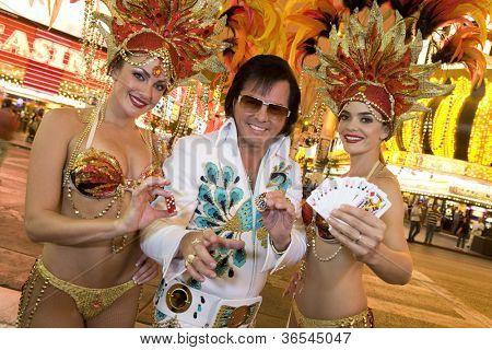 Elvis impersonator standing with casino dancers