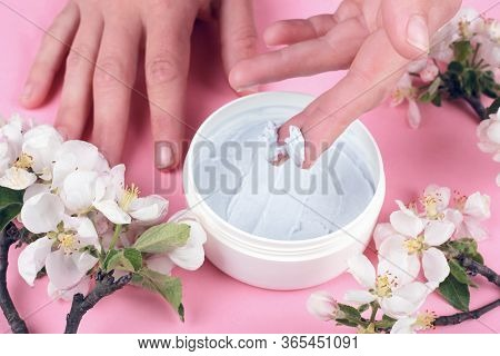 Body Scrub On A Pink Background With White Flowers Of Apple, Hands Applying Scrub Close Up, Skin Car