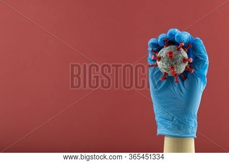 Wooden Hand Model Wearing Blue Gloves And Holding Ball Similar To Coronavirus Cells.