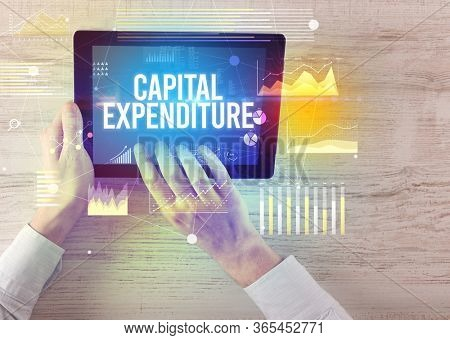 Close-up of hands holding tablet with CAPITAL EXPENDITURE inscription, modern business concept
