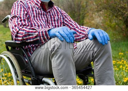 Close Up Picture Of Disabled Elderly Man's Hand Wearing Gloves In Time Of Covid-19 Pandemic, Sitting