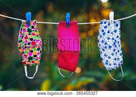 Face Masks With Different Style Prints Hang And Dry On Clothespins Outdoors At Sunset
