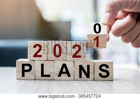 Businessman Hand Holding Wooden Cube With Flip Over Block 2020 To 2021 Plans Word On Table Backgroun