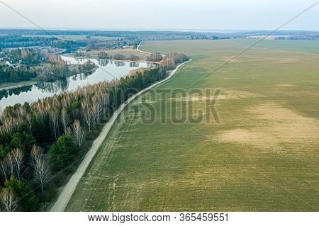Aerial View Of Country Road Between Green Fields And Blue Lake. Rural Landscape