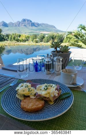 Eggs Benedict With Hollandaise And Hash Browns Served On A Plate Outside. Al Fresco Poached Eggs Bre