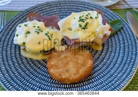Eggs Benedict With Hollandaise And Hash Browns Served On A Plate Outside