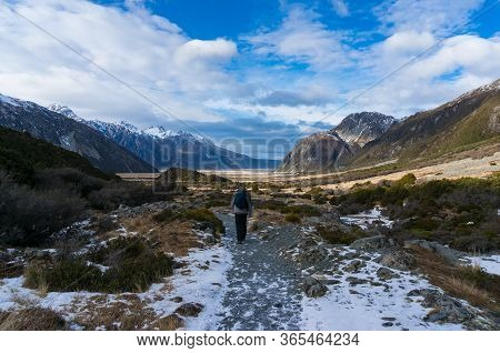 People Hiking. Winter Mountain Landscape With Foot Path And Snow Covered Mountains. Nature Tourism I