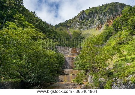 Dam Wall With Mountain On The Background And Green Forest. Dam Wall In The Forest Nature Background